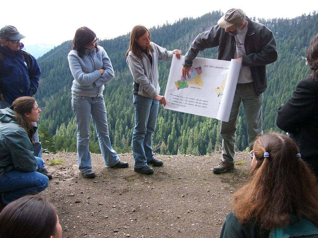 Description: Andrews scientist Fred Swanson explains the Blue River Management Plan to a tour group.