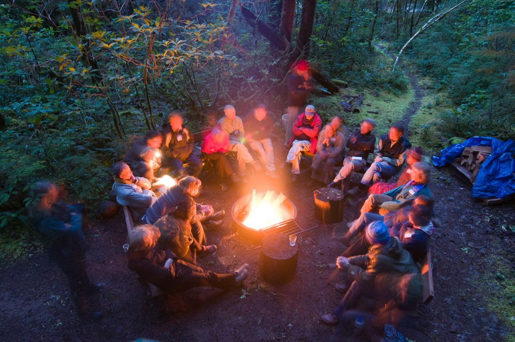 group of people sitting at a campfire