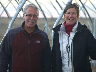 man and woman standing in front of greenhouse skeleton