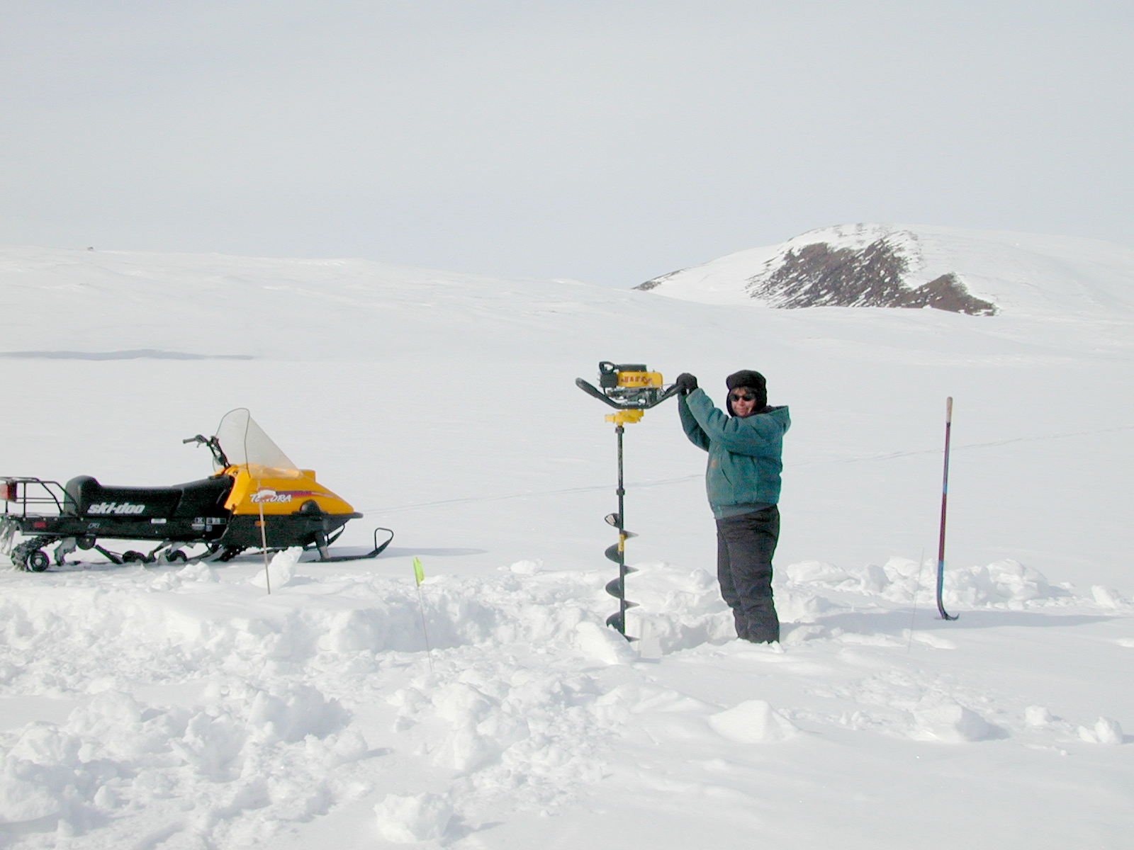 snowy landscape with a person using augur to dril through ice.