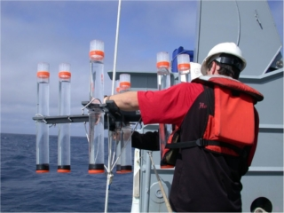 graduate student examining water collectors aboard ship