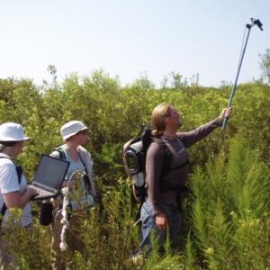 group of three students holding spectrometer aloft