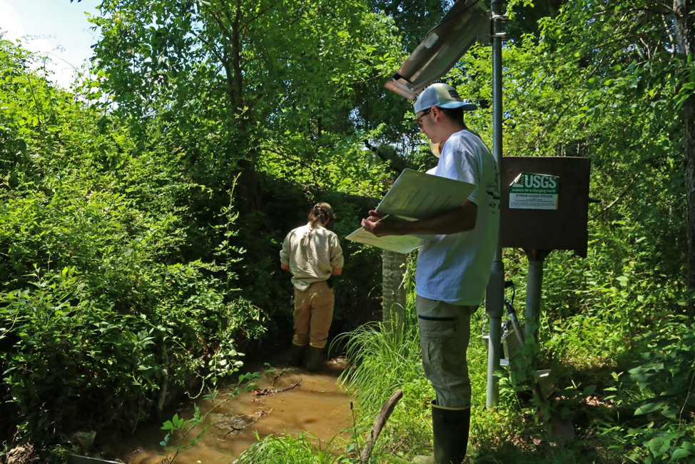 Student Nate Vandiver collects stream monitoring data with the BES team.