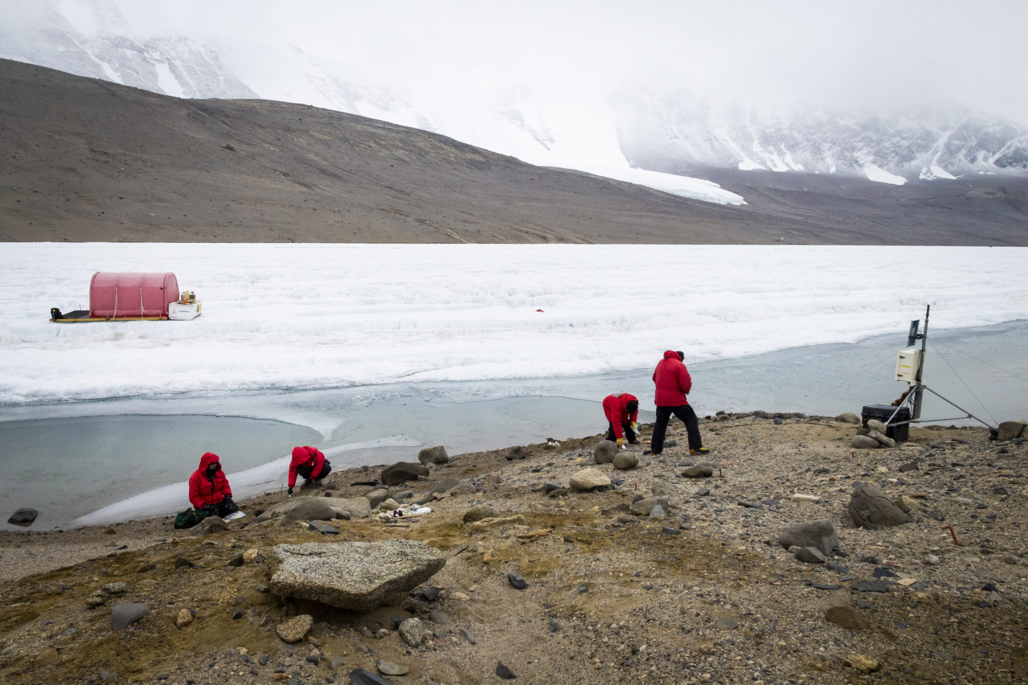 The Wormherders take soil samples from the SLIME experiment site on the northern shore of Lake Bonney. On their left is the dive hut used by other LTER scientists who dove under the ice to collect lake sediment samples. On their right is a sensor station that records information from buried soil moisture sensors on the lakeshore.