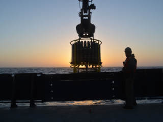 CTD instrument on ship with sunset in background