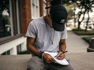 person in black baseball cap, writing in notebook