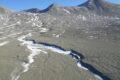 frozen streams emerging from a rocky, gray landscape